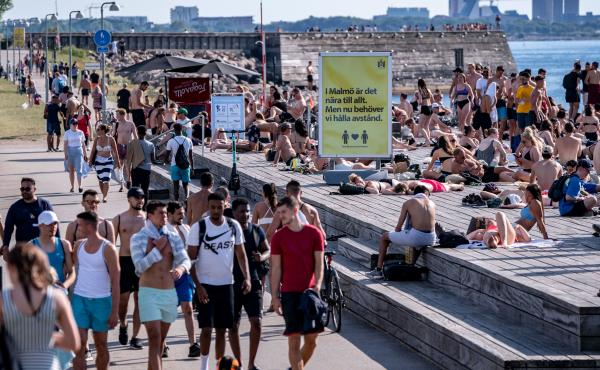 Sweden's top disease expert says a surge in new coronavirus cases is a result of more testing. Here, people enjoy the sun and water at a bathing jetty in Malmo, Sweden, on Thursday alongside a sign instructing the public to maintain social distancing.