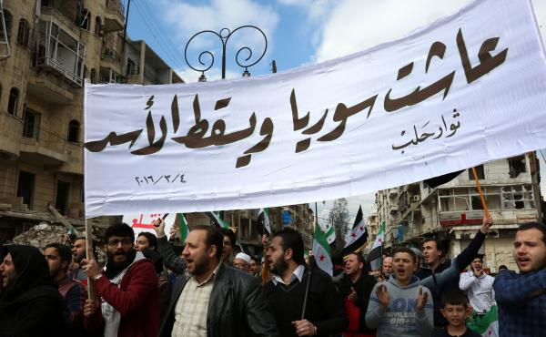 """As the ceasefire took hold this week, Syrians lost no time returning to the streets to protest the Assad regime. Marchers hold a banner reading """"Long live Syria, down with Assad"""" during an demonstration in the rebel-controlled side of Aleppo on Friday."""