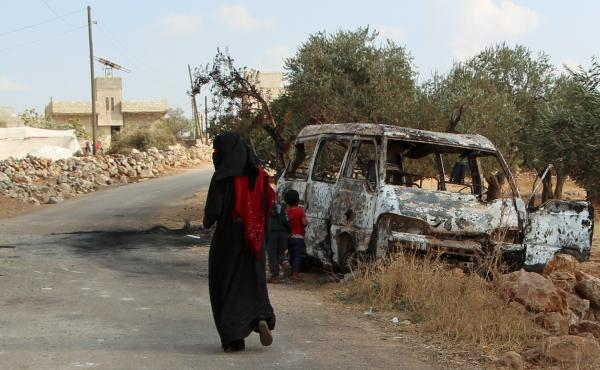 A woman walks past a wrecked van near the northwestern Syrian village of Barisha. Local residents and medical staff tell NPR that noncombatant civilians were killed and injured in the van the night of the U.S. raid on the compound of ISIS leader Abu Bakr