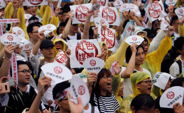 """Demonstrators protest against what they called """"red media"""" influence in Taiwan during a rally against pro-China media in front of the president's office building in Taipei on June 23. With a presidential election in January, Taiwan is bracing for a new de"""