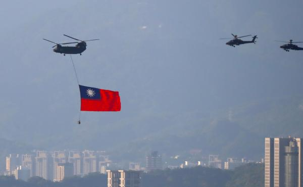 A military helicopter carrying a Taiwanese flag flies near the Taipei 101 building as part of the rehearsal ahead of the Double Ten National Day celebration in New Taipei, Taiwan, on Tuesday.