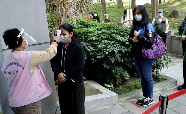 People line up for temperature checks at the Xinyi District Health Center in Taipei on April 14.