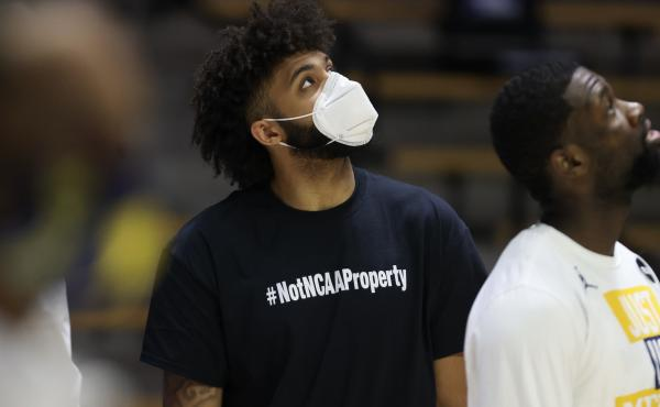 """Wearing a shirt that says, """"#NotNCAAProperty,"""" injured University of Michigan basketball player Isaiah Livers looks on prior to his team's NCAA tournament game against Texas Southern on March 20. On Wednesday the U.S. Supreme Court hears a case testing th"""