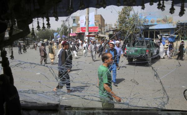 Afghans are seen through a shattered windshield of a bus after an explosion in Kabul, Afghanistan. A suicide car bomber targeted the police headquarters in western Kabul on Wednesday.