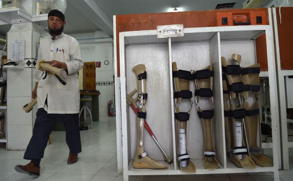 The Taliban say the Red Cross may resume its work in Afghanistan, more than five months after threatening the group. In this photo from March, an orthopedic technician walks past artificial limbs in a workshop at the International Committee of the Red Cro