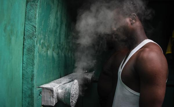 Tanzania is now endorsing COVID-19 vaccines. But for many months, its leaders said that vapors could prevent the disease. Above: A man inhales at a booth installed by an herbalist in Dar es Salaam.