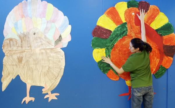 A teacher hangs up a brightly colored paper turkey painted by her students in 2007 in Corpus, Christi, Texas.