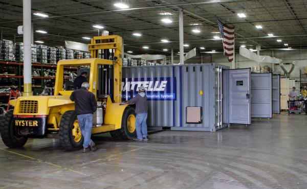 Workers inside a warehouse in Columbus, Ohio, prepare Battelle's decontamination units for deployment.