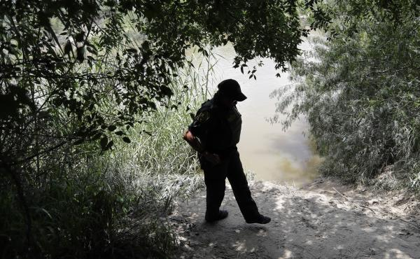 A U.S. Border Patrol agent walks along the banks of the Rio Grande River near McAllen, Texas. Migrant families often cross the river illegally to enter the U.S.
