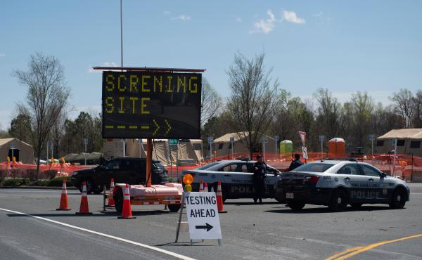 Healthcare professionals screen people at a testing site organized by the Maryland National Guard in a parking lot at FedEx Field on March 30, 2020 in Landover, Md.