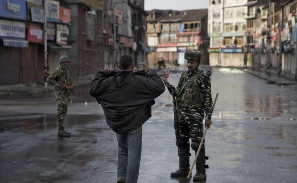 An Indian paramilitary soldier orders a man to lift his robe before frisking him in Srinagar on Thursday.