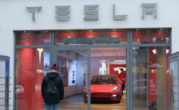 A man stands outside a Tesla dealership in Berlin on Jan. 4. On Friday, Tesla announced it would lay off 7 percent of its workforce, cutting some 3,000 jobs.