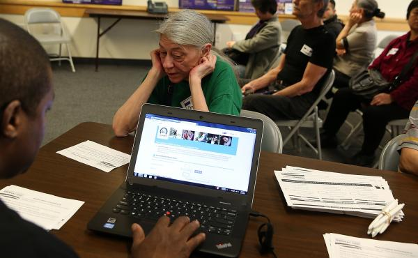Christine Moyer checks out options at a health insurance enrollment fair on March 18 in San Francisco.