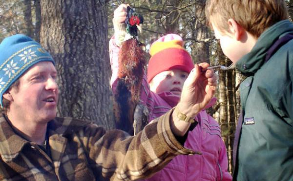Jeff Potter feeds roadkill pheasant to his kids, Lucy and Henry.