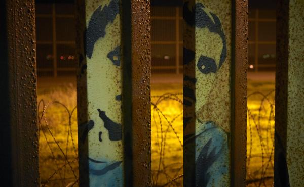An image of a boy is painted on the bars of the border wall, in front of coils of razor wire, seen from Tijuana, Mexico. President Trump's proposal to end the partial government shutdown includes funding for more border wall, but also provisions that furt
