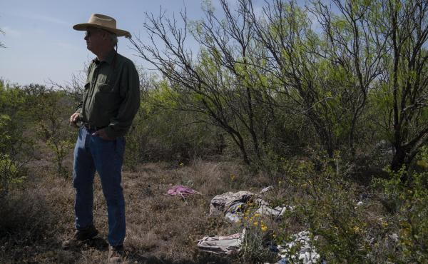 Rancher Hugh Fitzsimmons stands next to a pile of debris migrants left behind once they crossed into the United States.