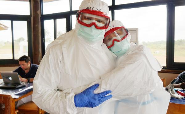 """How do siblings get around the """"no touching"""" rule during the Ebola outbreak in Sierra Leone? Alex and Jen Tran grabbed a rare hug when they were geared up for training."""