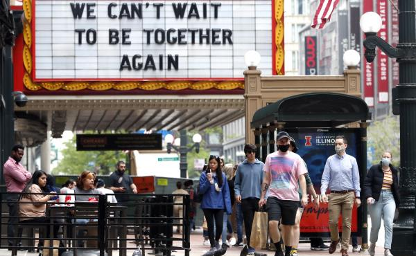 People walk near the Chicago Theatre on Tuesday in the city's Loop community. The Centers for Disease Control and Prevention eased its guidelines on the wearing of masks, saying fully vaccinated Americans don't need to cover their faces anymore in most se