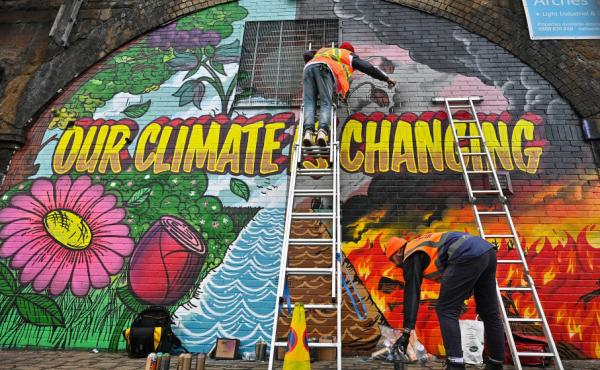 Artists paint a mural on a wall near Scottish Events Centre (SEC) in Glasgow, which will host the U.N. climate summit starting Sunday.