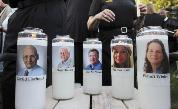 In this June 29, 2018, file photo, pictures of five employees of the Capital Gazette newspaper adorn candles during a vigil across the street from where they were slain in the newsroom in Annapolis, Md.