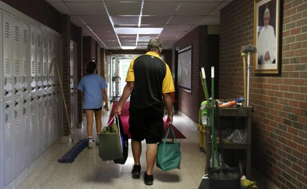 Cesa Pusateri, 12, and her grandfather, Timothy Waxenfelter, principal of Quigley Catholic High School, leave with his collection of speech and debate books after the closure of the school in Baden, Pa., on June 8, 2020. According to the National Catholic