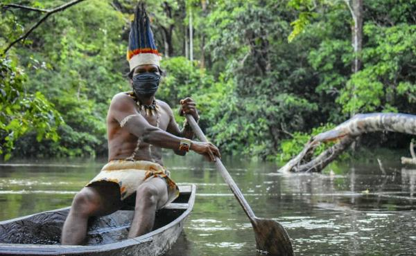 A Colombian Huitoto man sails on a raft along the Takana river in Leticia, Amazonas department, Colombia, on May 20, during the coronavirus pandemic.