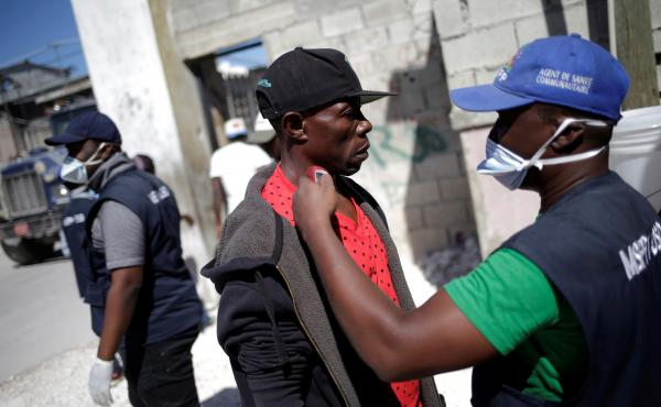 A worker with Haiti's Ministry of Public Health and Population checks the temperature of a Haitian man coming from the Dominican Republic on March 5.