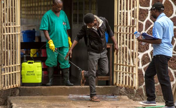 A worker disinfects shoes outside the Ebola security zone at a hospital in Mbandaka in the Democratic Republic of the Congo.