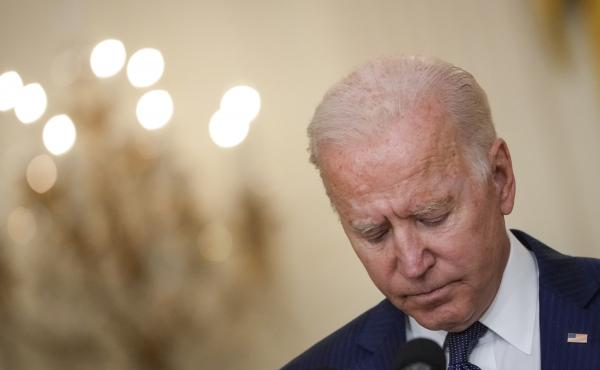 President Biden bows his head in a moment of silence Thursday as he speaks about the situation in Afghanistan from the White House's East Room.