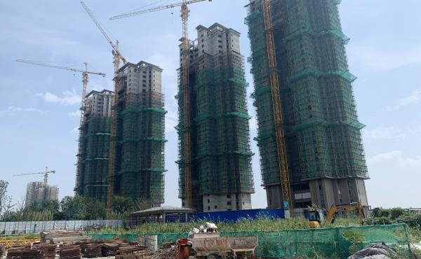 Half-finished apartment towers are part of Evergrande's Cultural City real estate project in Taicang, China. The firm has run out of money to finish the buildings as regulators force developers to pay back debts.