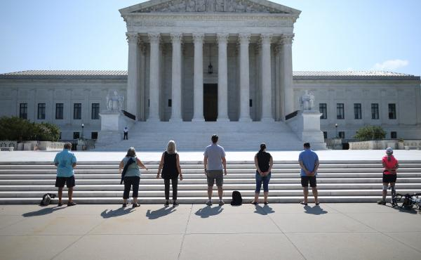 Demonstrators pray in front of the U.S. Supreme Court on July 8, a day the court ruled that employers with religious objections can decline to provide contraception coverage under the Affordable Care Act. With the death of Ruth Bader Ginsburg, the ACA's f