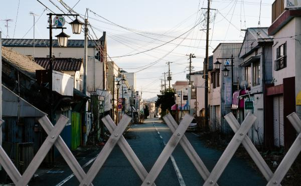 A view over a gate blocking off the old downtown of Okuma, in Fukushima Prefecture. Fukushima was forever changed by one of the world's biggest nuclear disasters nearly a decade ago.