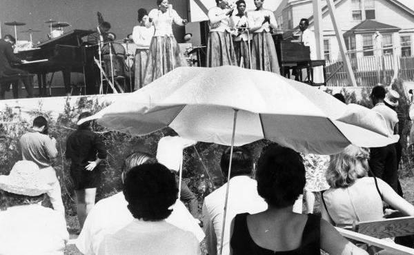 Fans sit under an umbrella as shade from the hot sun during the Newport Jazz Festival in Newport, R.I., on July 8, 1962.