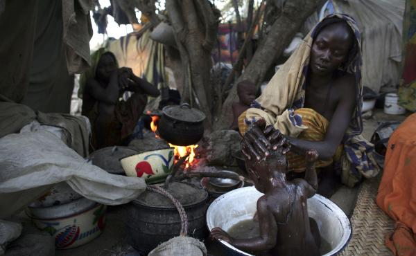 A woman from Chad washes her baby at a site for internally displaced persons. They had fled their village after an attack.
