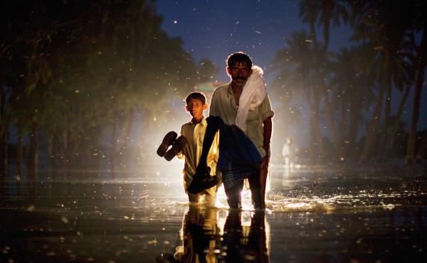 A Pakistani man and boy walk through floodwaters on Aug. 22, 2010, in the village of Baseera in Punjab.