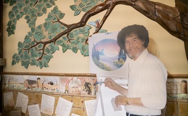 A life size cut out of Bob Ross stands up against the wall where the historical tree of the Franklin Park Arts Center is painted. Bob Ross Inc. is located in Herndon, Va., which is only 27 miles from the exhibit. According to managing director, Elizabeth