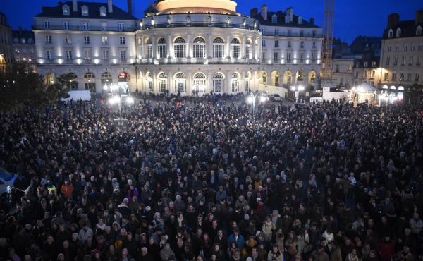 People gather in front of City Hall in Rennes, western France, in a show of respect for victims.