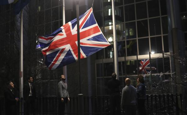 Officials lower and remove the Union Jack from the European Parliament building in Brussels on Friday. As the U.K. prepared to bring to an end its decades-long membership in the European Union, the bloc's top officials on Friday pledged to continue playin