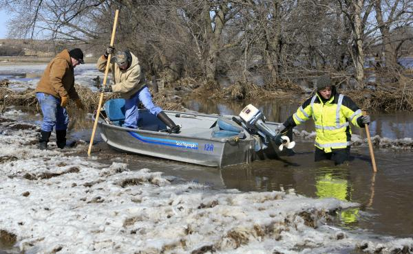 Tom Wilke, his son Chad, and Nick Kenny launch a boat into the swollen waters of the Elkhorn River to check on Witke's flooded property, in Norfolk, Neb., on Friday, March 15.