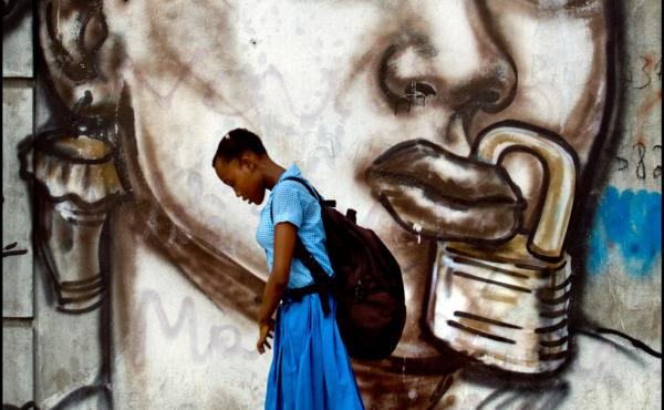 A student at a girl's school in Port-au-Prince walks past a mural by a famous Haitian street artist.