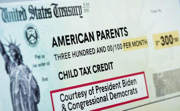 A child tax credit poster is displayed during a news conference in Washington, D.C., on July 15. Early data shows that after the child tax credit payments went out this summer, the number of households with children who experience food insufficiency dropp