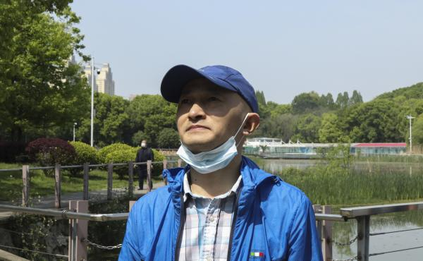 "Zhang Hai stands on a bridge where he took his father out for a walk only about four months earlier. His father died of the novel coronavirus on Feb. 1. ""The scenery is still here, but the person is gone,"" he sighs. He says he frequently comes to this par"