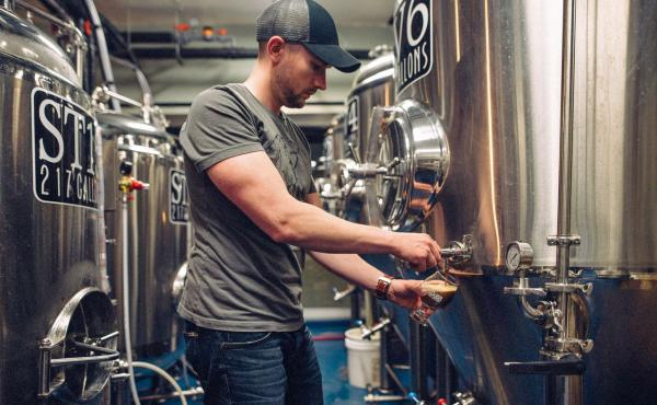 """Medusa Brewing Company co-founder Keith Sullivan checks on the beer in the brewing area. """"There are very few big breweries that have this family, community, connected feel. That's what we're selling,"""" he says."""