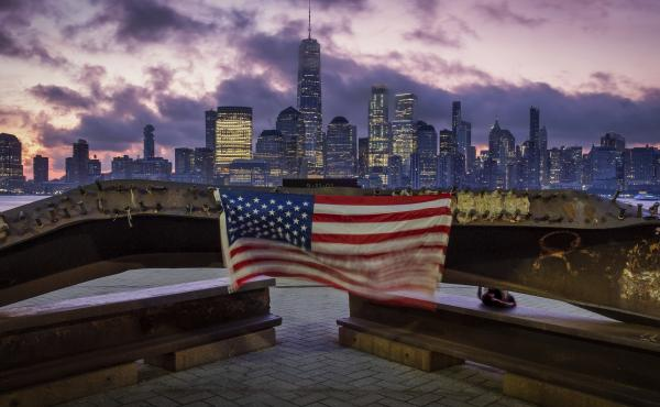 A U.S. Flag hanging from a steal girder, damaged in the Sept. 11, 2001 attacks on the World Trade Center, blows in the breeze at a memorial in Jersey City, N.J., Sept. 11, 2019 as the sun rises behind the One World Trade Center building and the re-develop