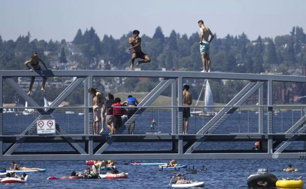 People jump from a pedestrian bridge at Lake Union Park in Seattle on Sunday as a record-setting heat wave blasts the Pacific Northwest.