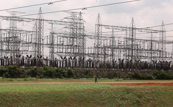 An employee walks past a power plant's electricity pylons in Lagos, Nigeria. Power shortages are particularly a problem for Nigeria's booming tech industry, which accounts for nearly 14% of the country's GDP.