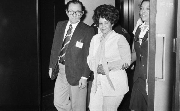 """Linda Taylor, 40, walks with her attorney T. Lee Boyd as they leave the Chicago Civic Center on March 8, 1977, during a recess in her trial. Dubbed the """"Welfare Queen,"""" Taylor was charged with bilking the State of Illinois out of $30,000 in bogus welfare"""