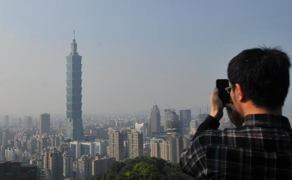 A tourist takes photos of Tower 101 in Taipei in 2013. Policy experts say the Taiwan Travel Act is a provocation for China because more visits to Taiwan by high-ranking U.S. officials could help boost the island's international profile.