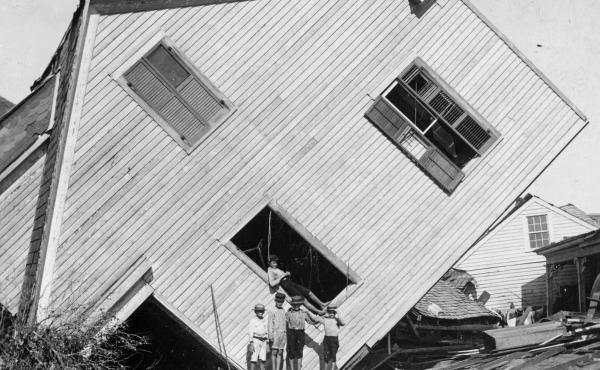A house tipped on its side, with several boys standing in front, after the Great Galveston Storm in Texas. The storm remains the worst natural disaster and the worst hurricane in U.S. history.