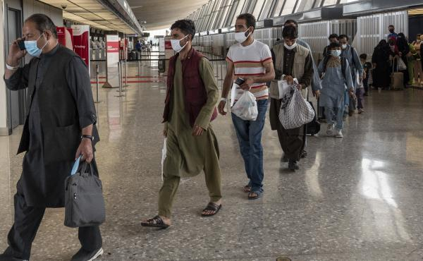 Refugees from Afghanistan are escorted to a bus after arriving and being processed Monday at Dulles International Airport in Virginia. The federal government is reportedly offering COVID-19 vaccines for Afghan arrivals at a site near the airport.